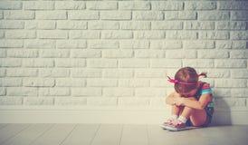 小孩女孩哭泣和哀伤关于砖墙 免版税库存图片