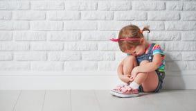 小孩女孩哭泣和哀伤关于砖墙 免版税库存照片