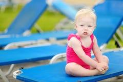 小孩女孩坐水池sunbed的  图库摄影