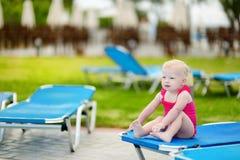 小孩女孩坐水池sunbed的  免版税库存照片