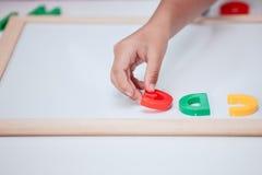 小孩女孩手戏剧和学会磁性字母表 库存图片