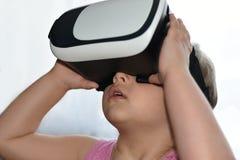 小孩女孩打与虚拟现实玻璃的一场比赛在白色背景,被增添的现实,盔甲,计算机游戏, enterta 免版税库存照片