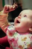 小孩女孩被激发关于吃鸡腿 免版税图库摄影