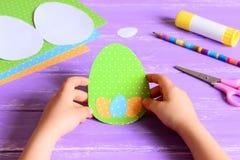 小孩子在手上拿着复活节纸牌 孩子做了复活节在蛋形状的贺卡 艺术活动的材料 库存照片
