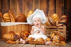 小孩子在篮子背景中烹调一个新月形面包与卷和面包的 免版税库存图片