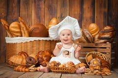 小孩子在篮子背景中烹调一个新月形面包与卷和面包的 库存图片