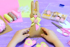 小孩子在他的手上拿着一只毛毡兔子 孩子做了毛毡与心脏的逗人喜爱的兔子复活节的 免版税库存图片