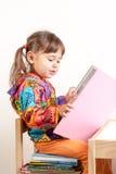 小孩子女孩阅读书坐被堆积的书 免版税库存照片