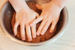 小孩子手在厨房里准备面团,烘烤曲奇饼 家庭leasure的接近的概念 免版税库存图片