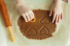小孩子手在厨房里准备面团,烘烤曲奇饼 家庭leasure的接近的概念 免版税库存照片