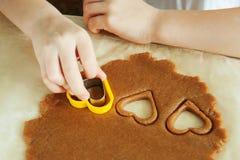 小孩子手在厨房里准备面团,烘烤曲奇饼 家庭leasure的接近的概念 免版税图库摄影