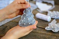小孩子显示圣诞节玩具 孩子在他的手上拿着圣诞节玩具 孩子缝合了从毛毡的一件圣诞树装饰品 库存图片