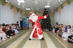 小孩子看起来圣诞老人跳舞在度假在幼儿园-俄罗斯,莫斯科, 2016年12月17日 图库摄影