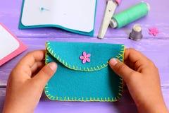 小孩子缝合了一个钱包毛毡 小孩子在他的手上拿着一个钱包 孩子概念的简单的手工制造工艺 免版税库存照片
