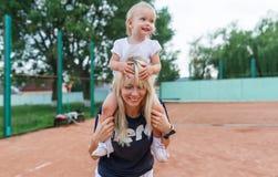 小孩子,一个小女孩坐微笑,笑,使用,获得乐趣在网球场的妈妈肩膀 图库摄影