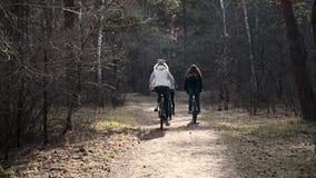 小孩子,三个女孩在秋天公园骑一辆自行车 活跃孩子和女孩姐妹有自行车的 t 股票视频
