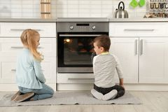 小孩小圆面包的等待的准备在烤箱的 库存图片