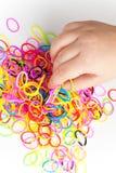 小孩手和堆小五颜六色的橡皮筋儿 库存图片