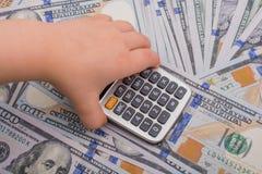 小孩拿着在美元钞票的计算器 库存照片