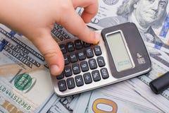 小孩拿着在美元钞票的计算器 免版税库存图片