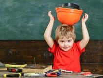 小孩拿着防护安全帽,由反面,黑板背景的盔甲 儿童逗人喜爱和可爱的投入的安全帽 库存照片