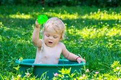 小孩有获得的蓝眼睛的女婴乐趣用水 库存照片