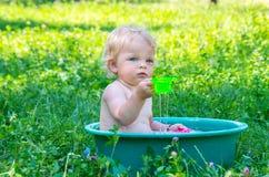 小孩有获得的蓝眼睛的女婴乐趣用水 库存图片