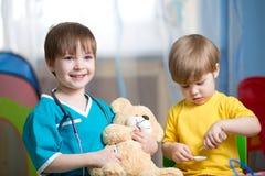 小孩有长毛绒玩具的戏剧医生 免版税库存图片