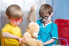 小孩有长毛绒玩具的戏剧医生 库存图片