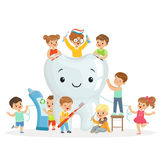 小孩照料并且清洗一颗大,微笑的牙 五颜六色的漫画人物 库存照片