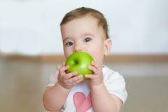 小孩用一个绿色苹果在他的手上 接近的纵向 库存照片