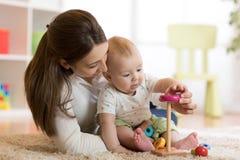 小孩男孩和他的妈妈在家使用与玩具 免版税库存照片