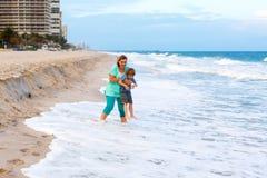 小孩男孩和母亲海滩的海洋 库存照片