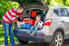 小孩男孩和父亲在离开前在汽车假期 免版税图库摄影