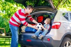 小孩男孩和父亲在离开前在汽车假期 库存图片