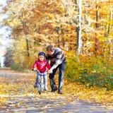 小孩男孩和父亲有自行车的在秋天森林里 免版税库存图片