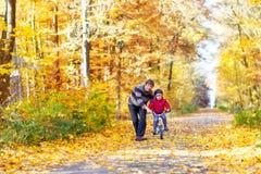 小孩男孩和父亲有自行车的在秋天 免版税库存图片