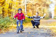 小孩男孩和父亲有自行车的在秋天 库存照片