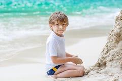 小孩男孩大厦在热带海滩的沙子城堡 库存图片