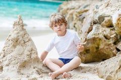 小孩男孩大厦在热带海滩的沙子城堡 免版税库存图片
