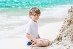小孩男孩大厦在热带海滩的沙子城堡 免版税图库摄影