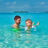 小孩男孩学会游泳与父亲 免版税库存图片