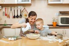 小孩男孩帮助母亲烹调姜饼干 愉快的家庭妈妈和孩子在周末早晨在家 关系 图库摄影