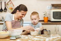 小孩男孩帮助母亲烹调姜饼干 愉快的家庭妈妈和孩子在周末早晨在家 关系 免版税库存图片