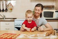 小孩男孩帮助母亲烹调姜饼干 愉快的家庭妈妈和孩子在周末早晨在家 关系 库存图片