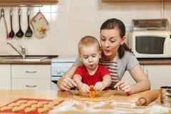 小孩男孩帮助母亲烹调姜饼干 愉快的家庭妈妈和孩子在周末早晨在家 关系 免版税库存照片