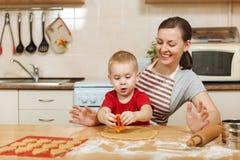 小孩男孩帮助母亲烹调姜饼干 愉快的家庭妈妈和孩子在周末早晨在家 关系 库存照片