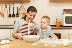 小孩男孩帮助母亲烹调姜饼干 愉快的家庭妈妈和孩子在周末早晨在家 关系 免版税图库摄影