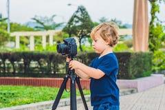 小孩男孩拍在一台照相机的照片在三脚架 免版税库存图片