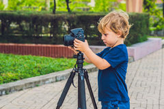 小孩男孩拍在一台照相机的照片在三脚架 免版税库存照片